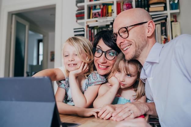 Família com três filhos em ambiente interno usando tablet