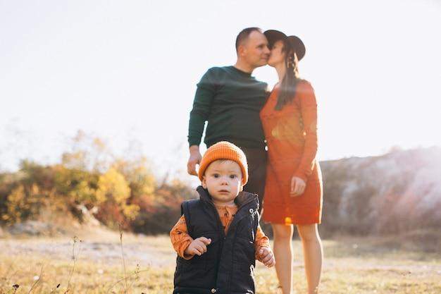 Família com um filho pequeno no parque outono