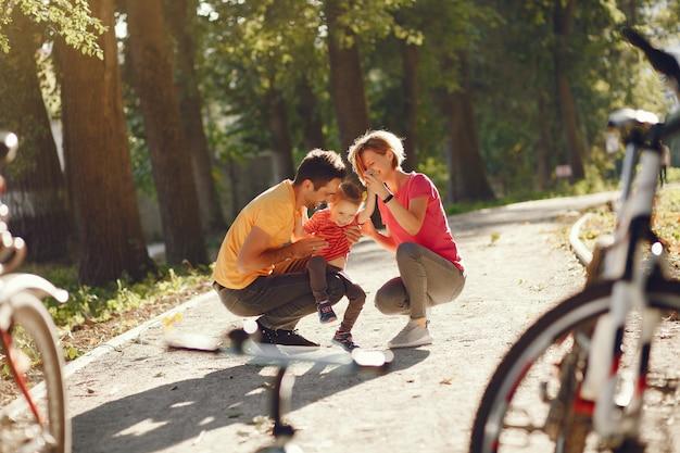 Família com uma bicicleta em um parque de verão