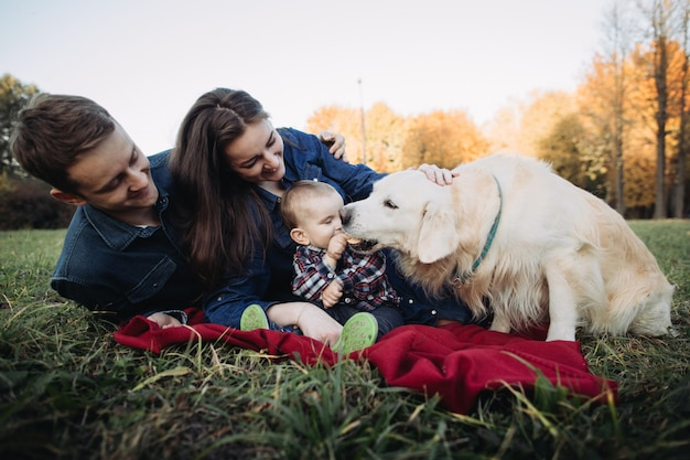 Família com uma criança e um golden retriever em um parque de outono
