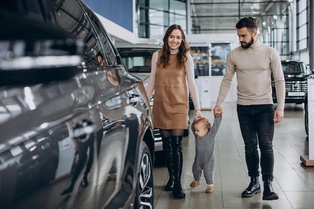 Família com uma menina escolhendo um carro em um salão de automóveis