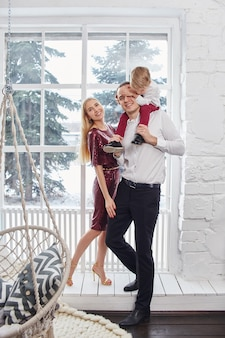 Família comemora natal e ano novo. mãe pai e filho se abraçam, feriado em família
