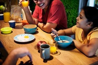 Família comendo na mesa de jantar juntos