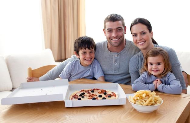 Família comendo pizza e batatas fritas em casa