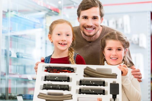 Família comprando ferrovia modelo na loja de brinquedos