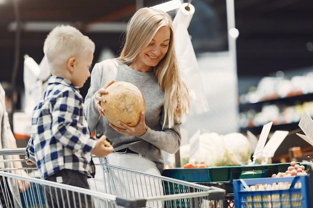 Família comprando mantimentos. mãe de suéter cinza.