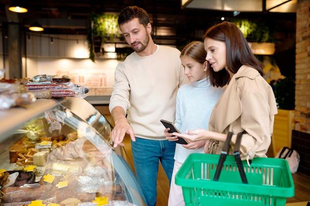 Família contemporânea de três pessoas escolhendo produtos de carne no supermercado enquanto jovem apontando para uma das salsichas em exibição