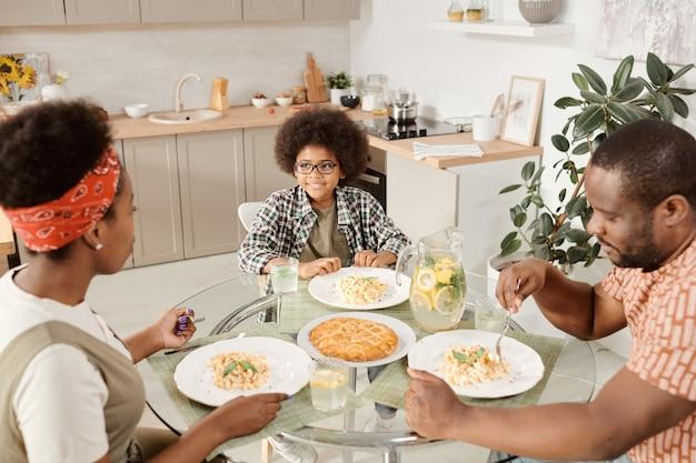 Família contemporânea de três pessoas servindo macarrão no jantar e torta de maçã na sobremesa