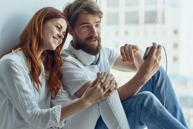Família conversando perto da janela tecnologia de alegria de romance