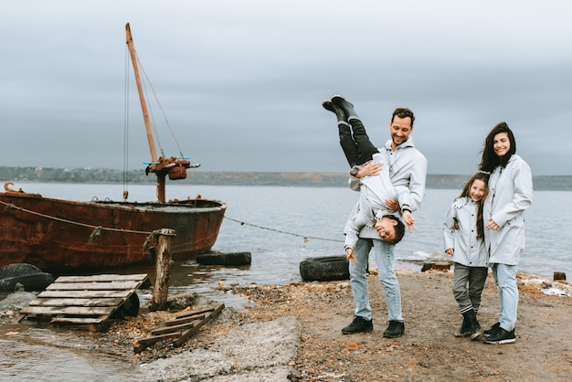 Família correndo e se divertir perto do mar em capa de chuva