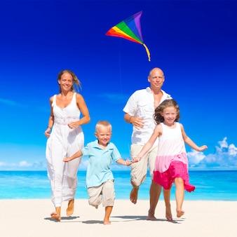 Família correndo na praia.
