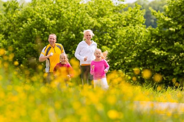 Família correndo no prado para fitness