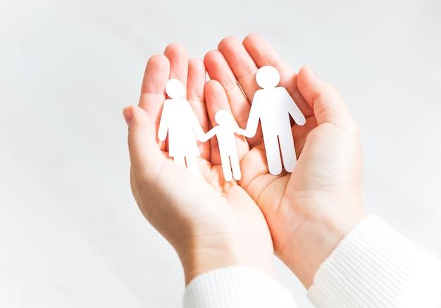 Família cortada em papel em duas mãos