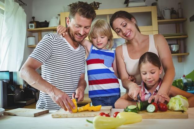Família cortar legumes na cozinha