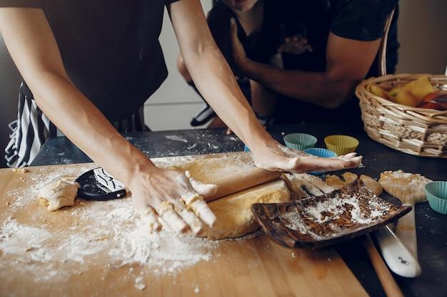 Família cozinha a massa para biscoitos na cozinha