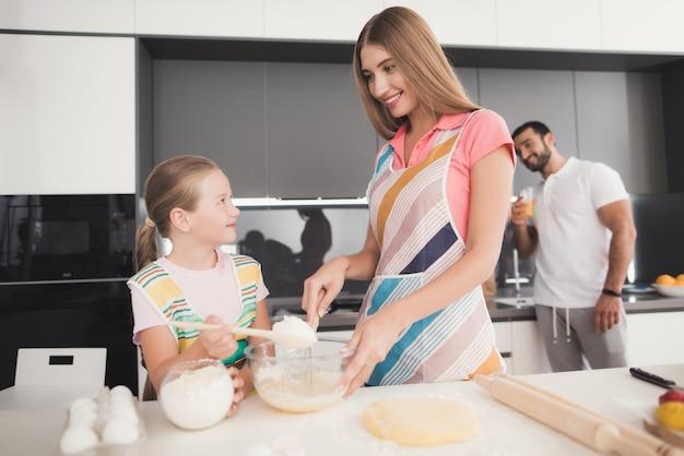 Família cozinha massa. mãe e filha preparam a massa.