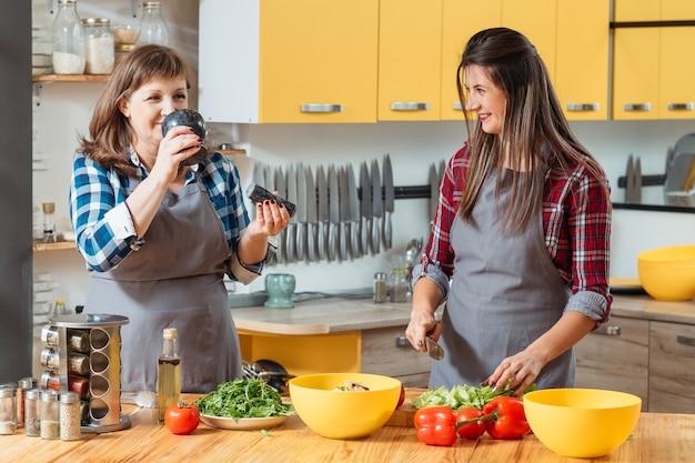 Família cozinhando e se comunicando na cozinha. mãe e filha juntas