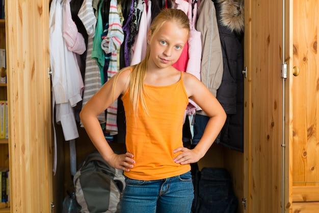Família, criança na frente de seu armário ou guarda-roupa