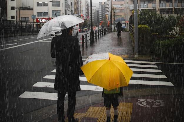 Família cruzando uma estrada em dia chuvoso