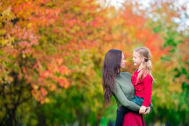 Família da mãe e da criança ao ar livre no parque no dia do outono