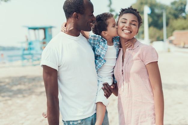Família da mãe, pai e filho na praia