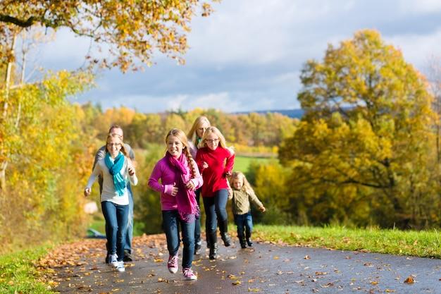 Família dar um passeio na floresta de outono