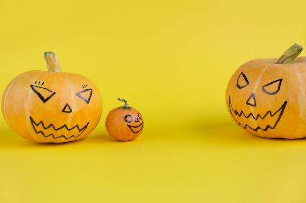 Família de abóbora de halloween com rostos malignos assustadores em pais e filhos de conceito de fundo amarelo.