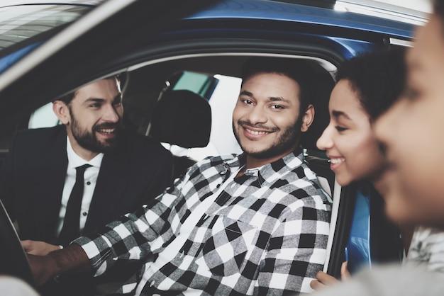 Família de afro árabe feliz comprando carro na concessionária.