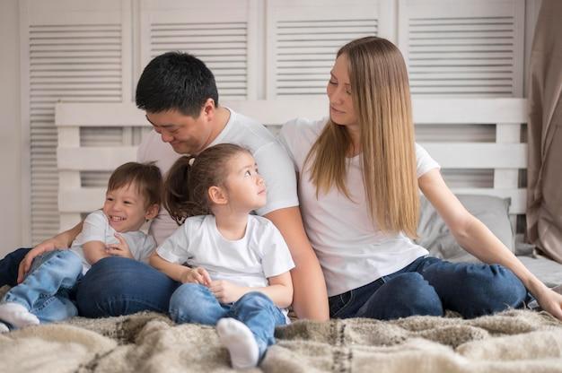 Família de alto ângulo em casa na cama