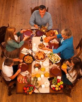 Família de alto ângulo sentada à mesa de jantar