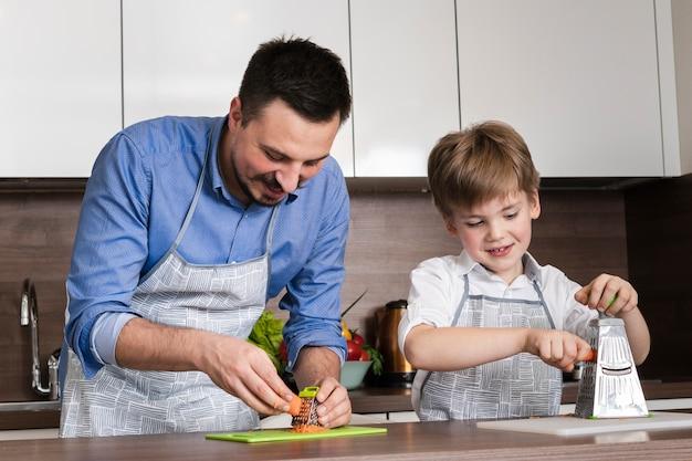 Família de ângulo baixo cozinhando juntos