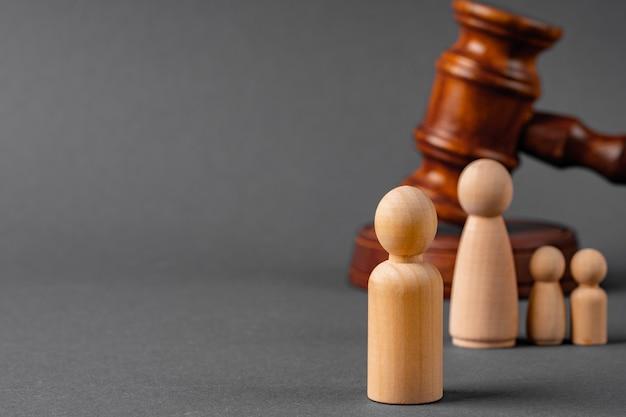 Família de brinquedo de madeira e malho de juiz. conceito de divórcio familiar