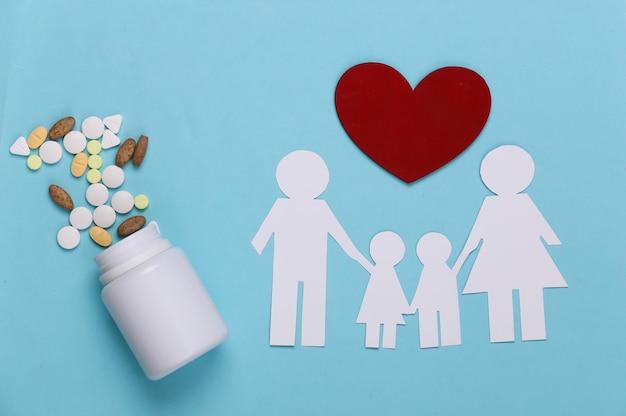 Família de corrente de papel, pílulas de garrafa e coração vermelho em azul, conceito de seguro saúde