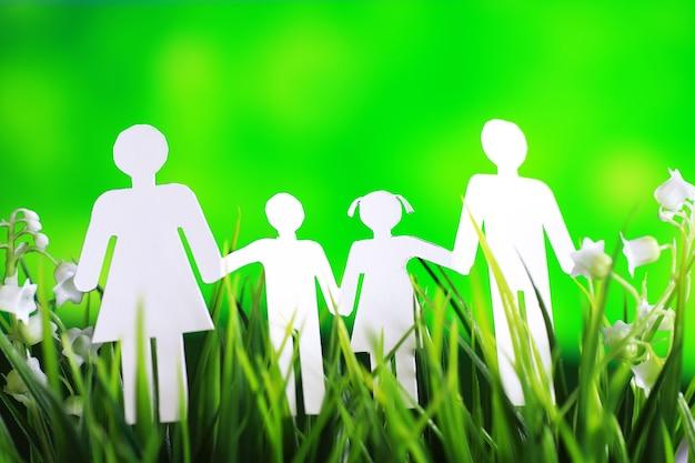 Família de correntes recortadas de papel com proteção de mãos em concha, conceito de segurança e cuidado. mãos com silhueta de papel recortado na mesa. conceito de cuidado familiar
