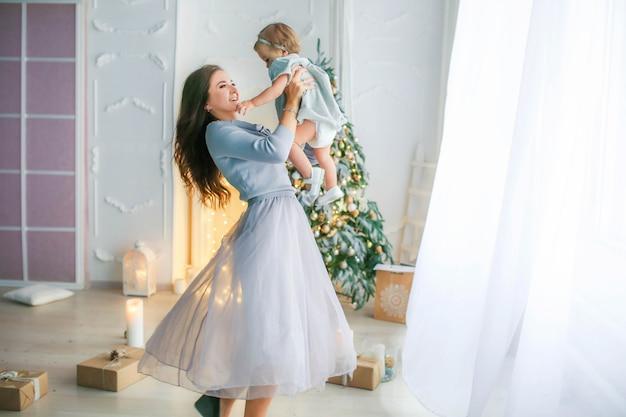Família de duas pessoas mãe e filha de 1 ano no contexto da foto da árvore de natal em cores brilhantes.