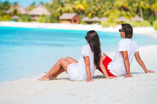 Família de duas pessoas na praia de areia branca durante as férias de verão