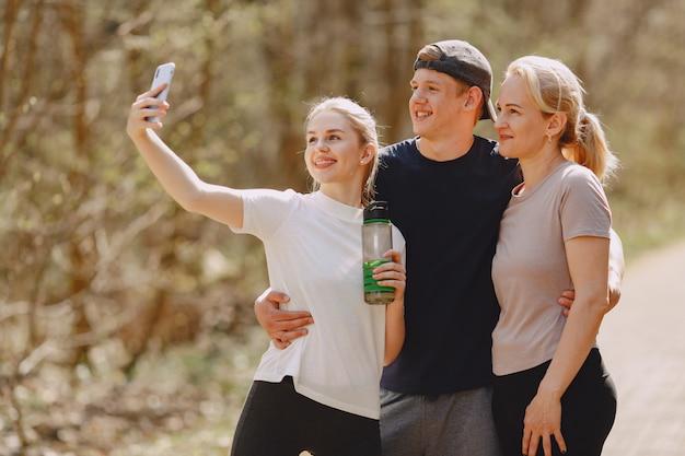 Família de esportes em pé em uma floresta de verão