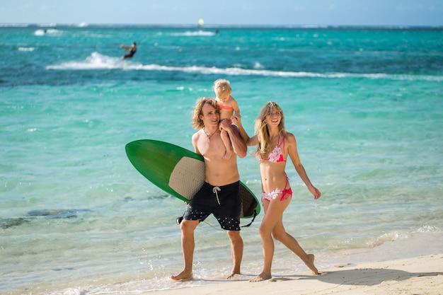 Família de esportes pai, mãe e filha caminhando na praia