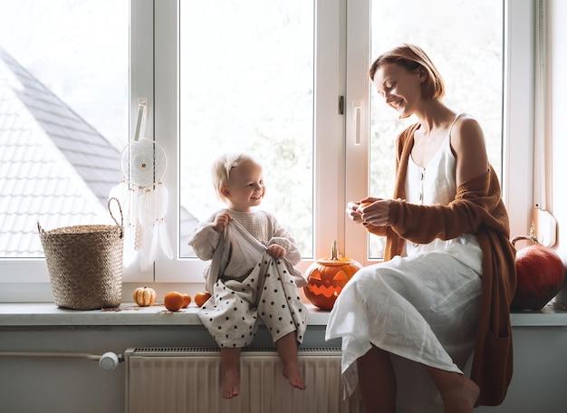 Família de estilo minimalista com criança se preparando para o halloween. feliz mãe e sua filha sentada perto da janela com escultura em abóbora cabeça jack lanterna e decoração de halloween em casa.