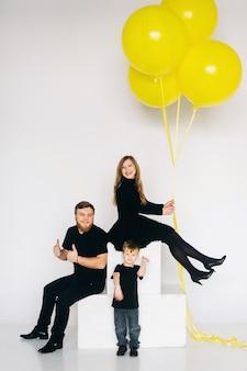 Família de estrela do rock com um grande balão amarelo. família elegante em roupas pretas