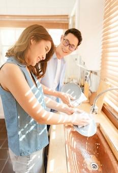 Família de feliz casal asiático lavando pratos juntos na cozinha depois do café da manhã.
