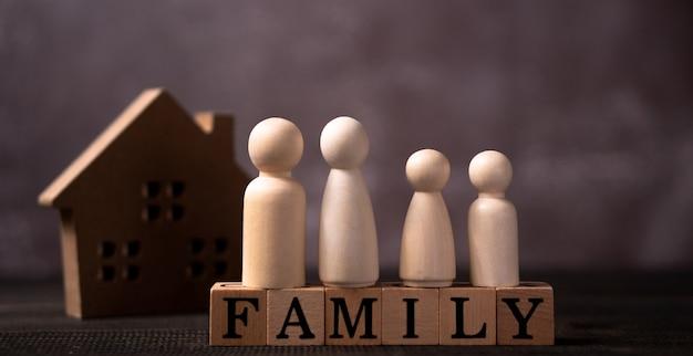 Família de figuras de madeira em pé no cubo de madeira que escreve a família de palavras na frente de uma casa de madeira.