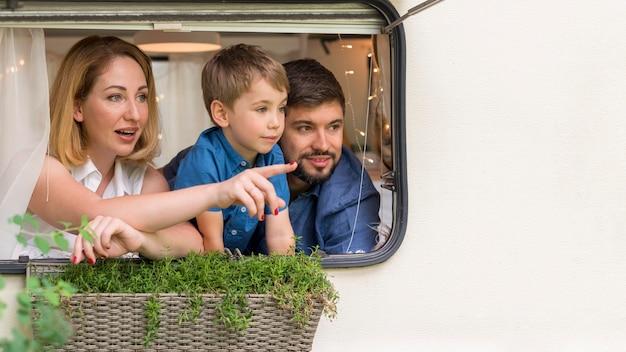 Família de frente olhando pela janela de uma caravana com espaço de cópia
