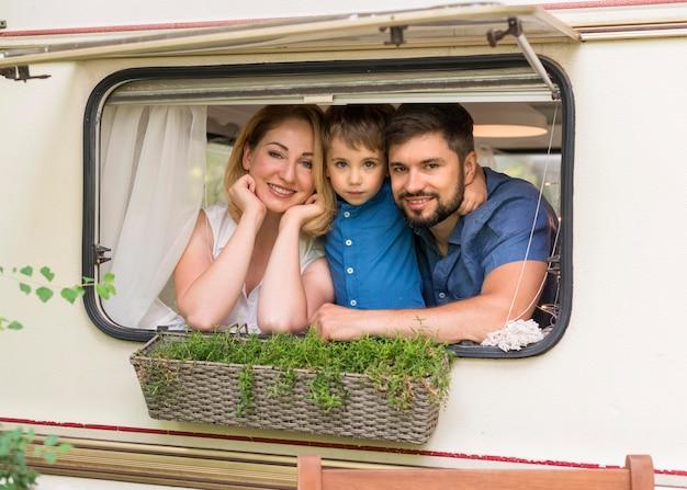 Família de frente olhando pela janela de uma caravana
