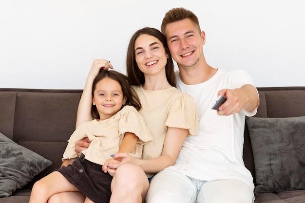 Família de frente sentada no sofá olhando para a tv