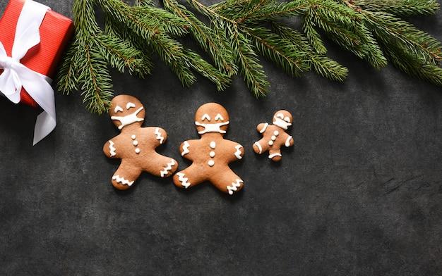 Família de gengibre em máscaras. fundo de natal com biscoitos de gengibre e presentes.