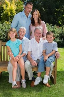 Família de geração multi feliz sentado no parque