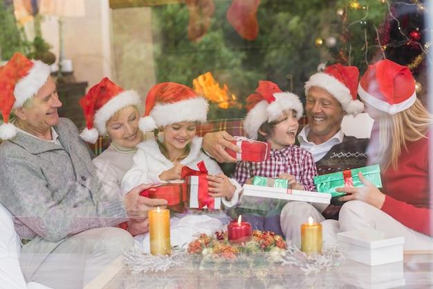 Família de geração multi segurando um monte de presentes no sofá