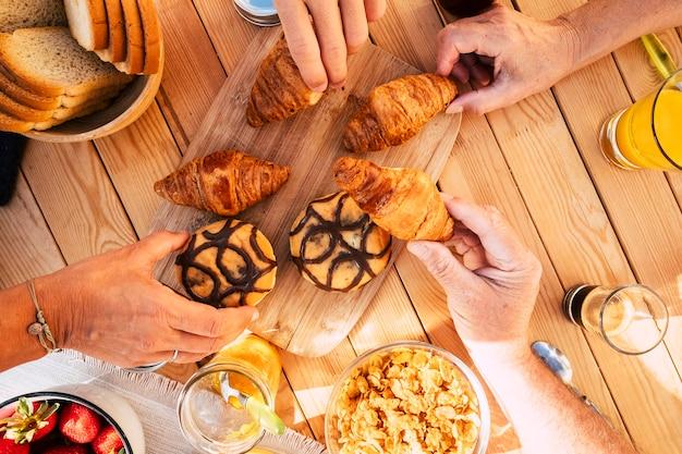Família de grupo de amigos, vista de cima vertical, comendo croissant e comida mista para a atividade matinal de café da manhã