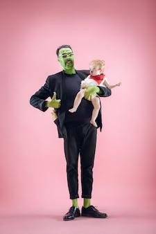 Família de halloween. pai feliz e filha recém-nascida em fantasia de halloween e maquiagem. tema sangrento: o louco maniak no fundo rosa do estúdio